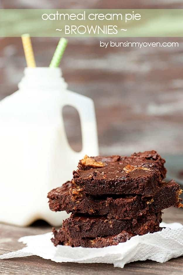 A stack of brownies in front of a mini jug of milk.