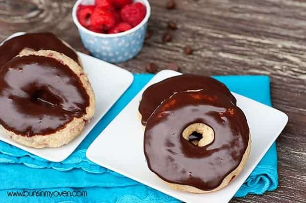 Two plates of chocolate donuts on a blue cloth napkin