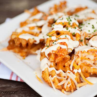 A closeup of buffalo chicken waffle fries on a Square white plate