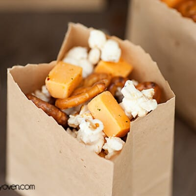 A close up of mini pretzels and popcorn in a paper bag.