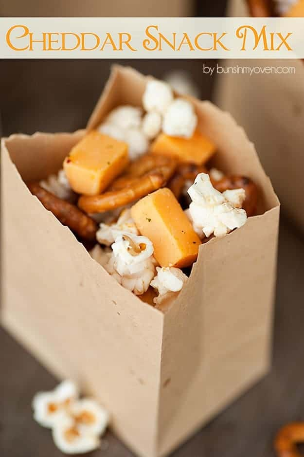 A close up of a popcorn and pretzel snack mix in a paper bag.