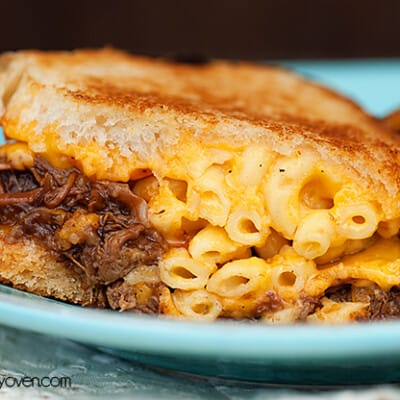 A close up of a plate of a macaroni and cheese sandwich.