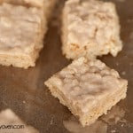Some small rice crispy treats on a baking sheet.