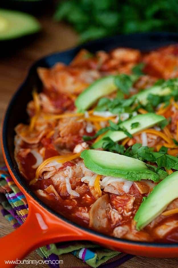A cast iron skillet of chicken, avocado, and enchilada sauce.