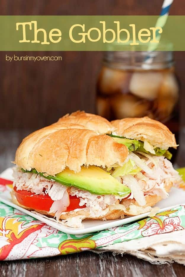 A close up of a turkey sandwich in front of a jar of iced tea