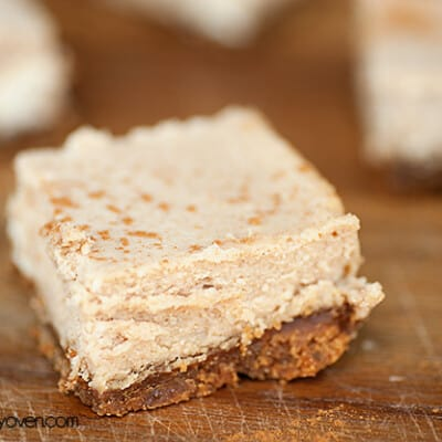 A close up of a cinnamon cheesecake on a wooden cutting board.