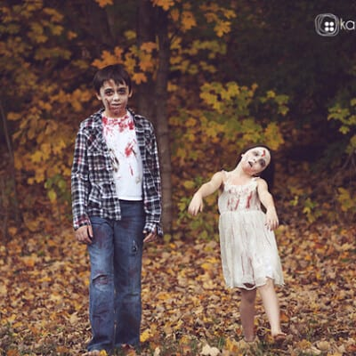 Two kids dressed as zombies in the woods.