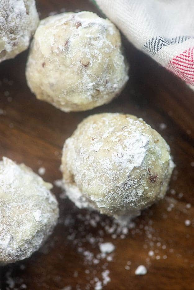 Three snowball cookies on a wooden serving tray.