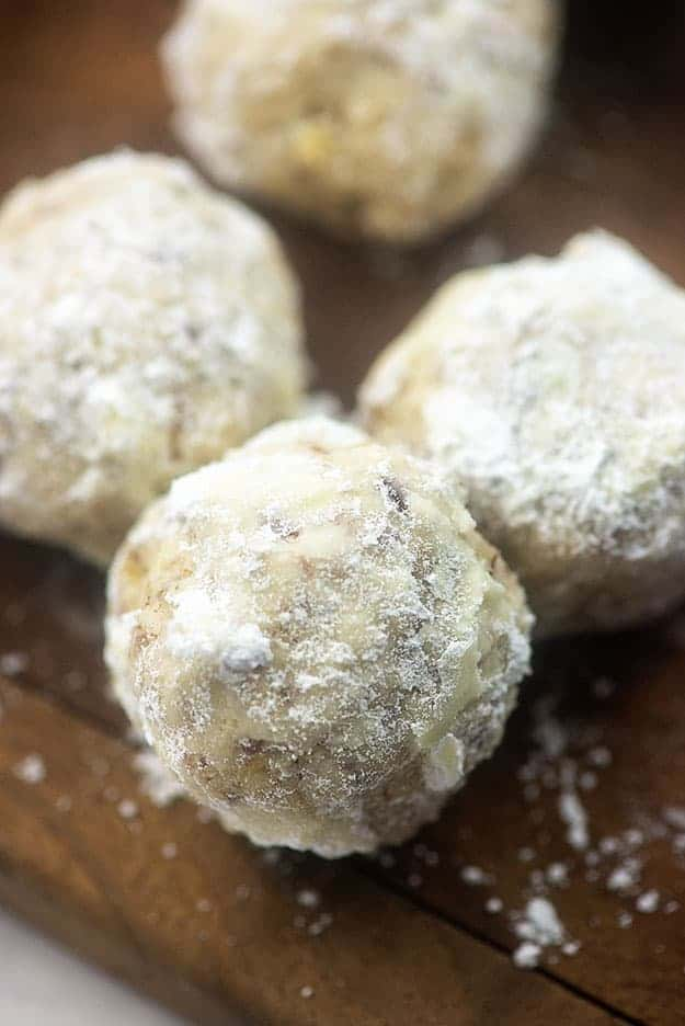 Three cookie balls covered in powdered sugar.