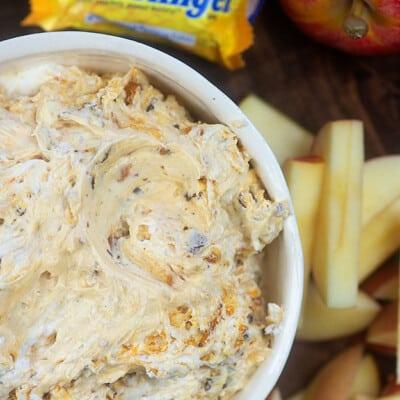 Butterfinger dip in a bowl near sliced apples.