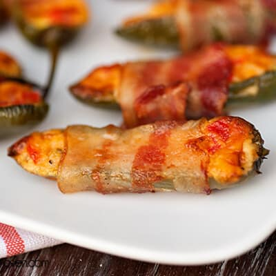 A close up of a bacon wrapped jalapeno pepper.