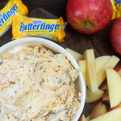 Butterfinger dip in a bowl next to candy bars and apples.