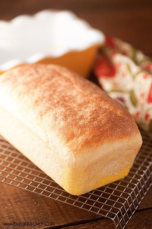 A close up of a loaf of bread on a wire cooling rack.