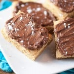 Chocolate fudge peanut butter bars on a square white plate.
