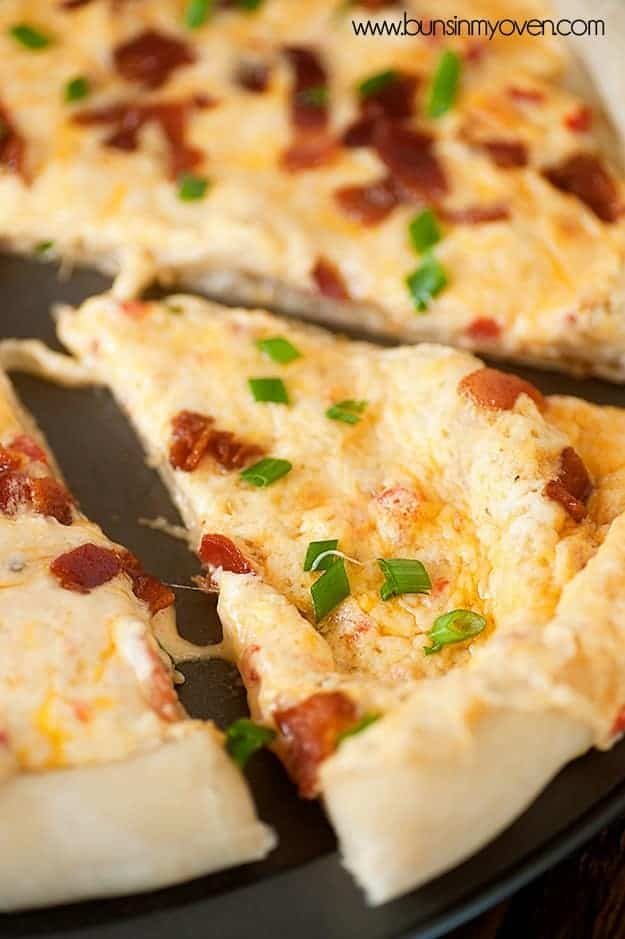 A slice of bacon and cheese pizza up close.