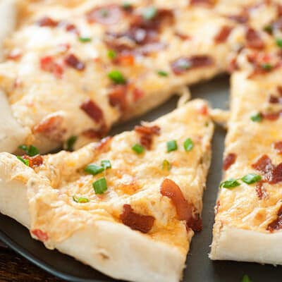 A close up of a slice of bacon cheese pizza cut from the rest of the pizza.