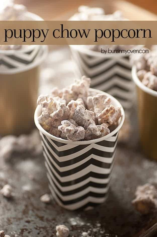 Puppy chow popcorn in a black and white striped paper cup.