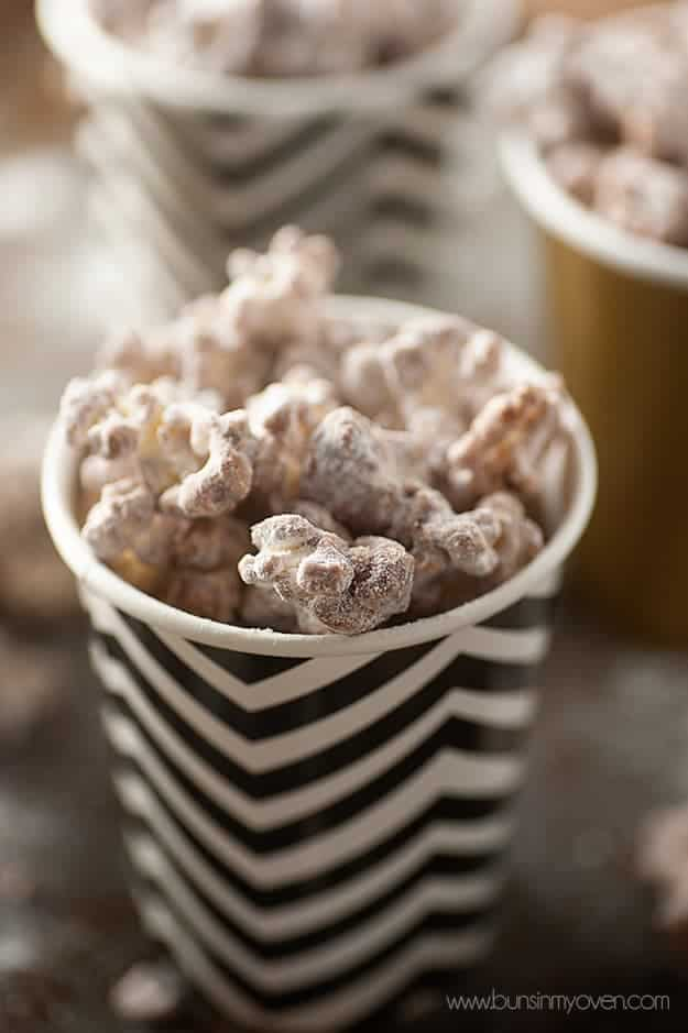 A close up of powdered sugar popcorn in a black and white cup.