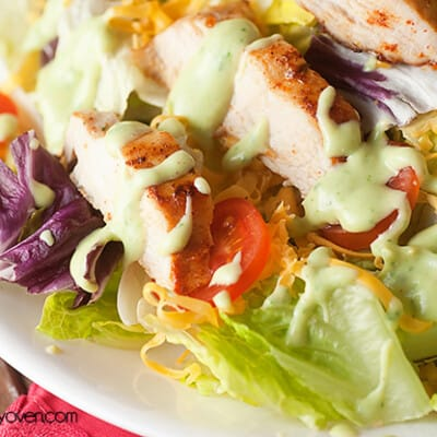 A close up of salad topped with chicken and avocado dressing.