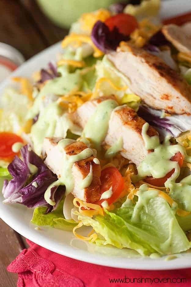 A plate of salad with grilled chicken on top.