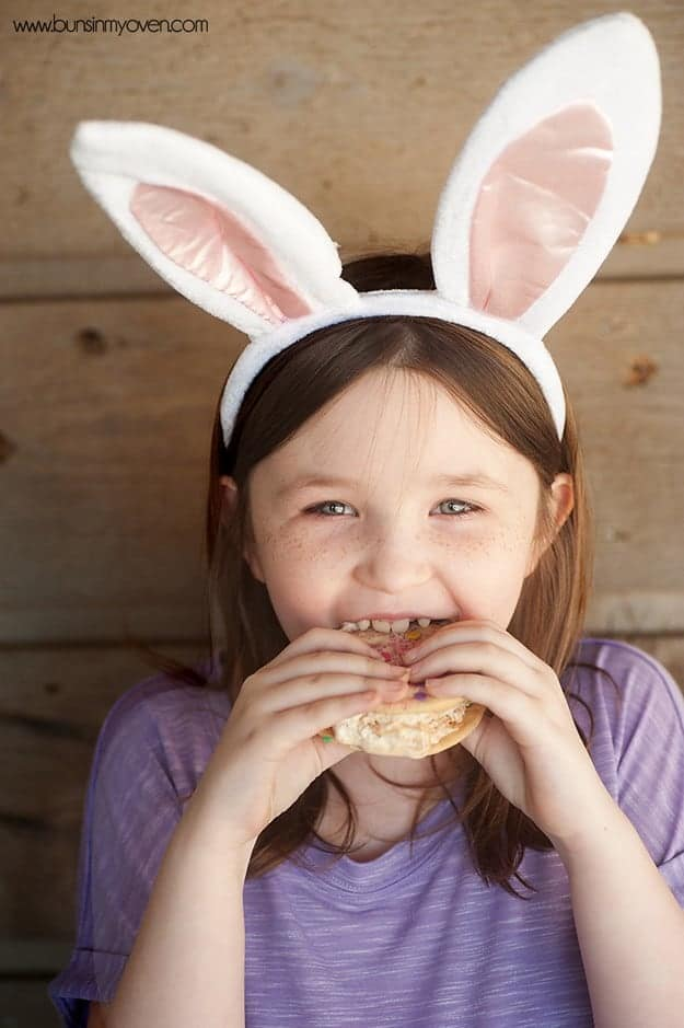 a girl wearing a bunny ear handband eating an ice cream sandwich