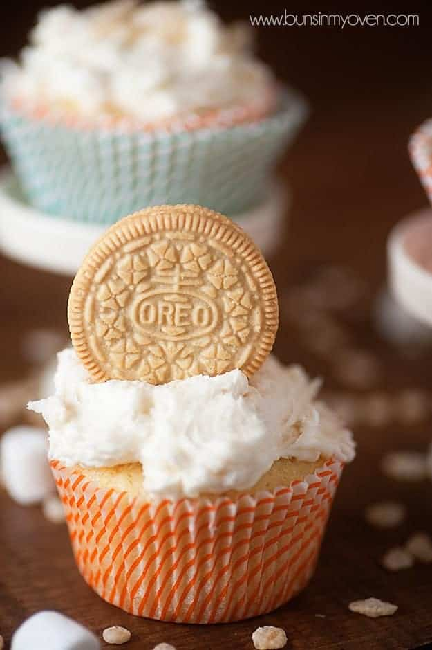 A vanilla oreo resting in icing on a white cupcake.