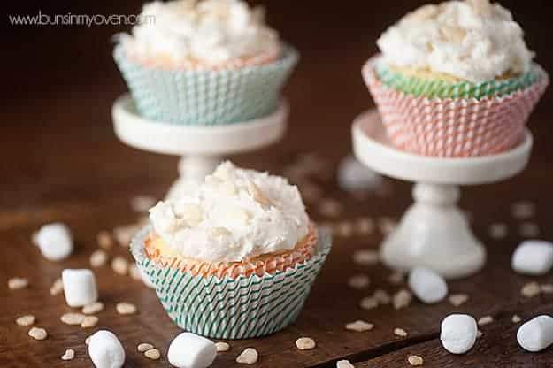 Three decorated cupcakes on a table surrounded by marshmallows and sprinkles.