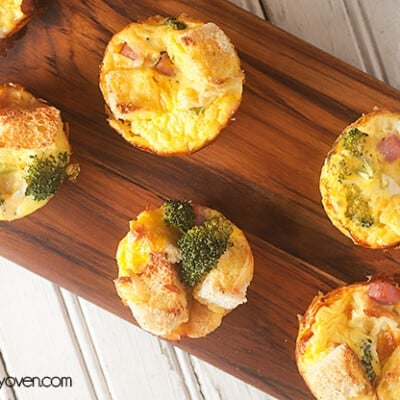 A narrow wooden cutting board with many ham strata muffins on it.