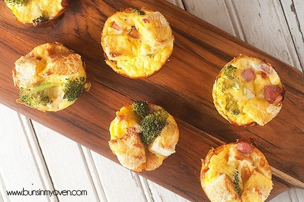 An overhead view of a dark narrow cutting board with ham strata muffins on it.