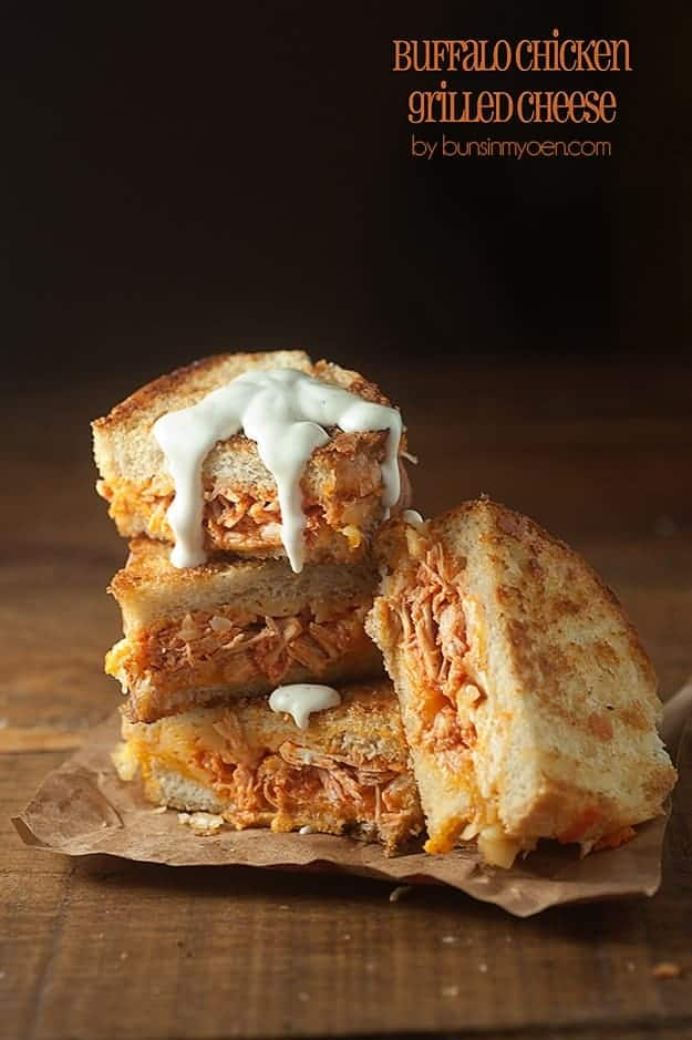 A buffalo chicken sandwich cut into four quarters on a wooden table.