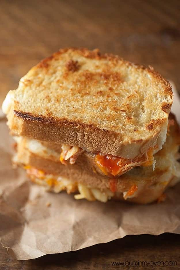 Overhead view of two stacked grilled cheese sandwiches on a table.