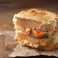 Two grilled cheese sandwiches with buffalo chicken stacked on a paper placemat.