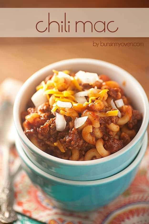 Macaroni noodles, chili, shredded cheese, and diced onions in a small white cup.