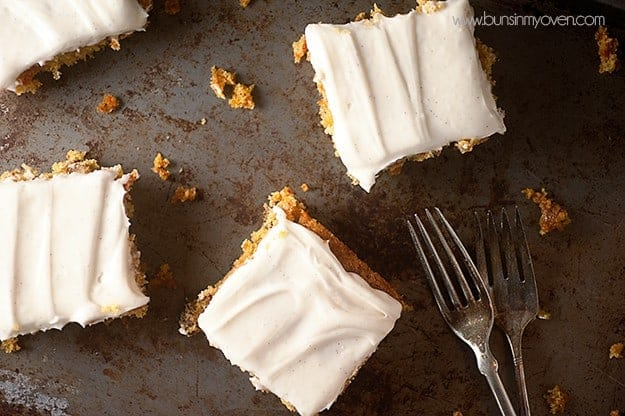 Several squares of carrot cake on a baking sheet with a couple forks.