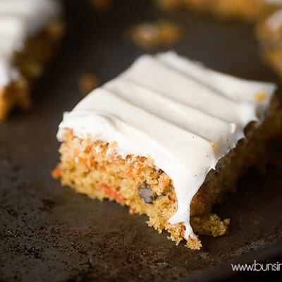 A square slice of carrot cake on a baking sheet.