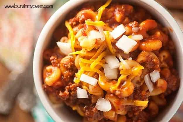 A close up of chili mac topped with shredded cheese.