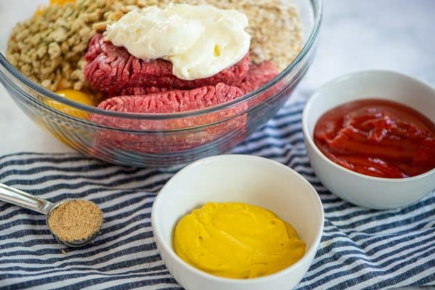 meatloaf mixture in glass bowl with ketchup and mustard in small bowls.