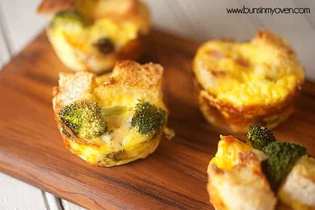 Muffin tin strata with broccoli and cheese on a wooden cutting board.