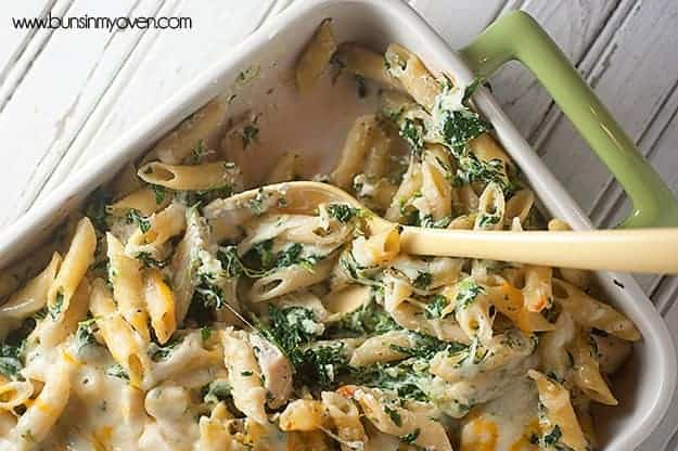 Spinach artichoke dip pasta with a serving removed from the baking dish.