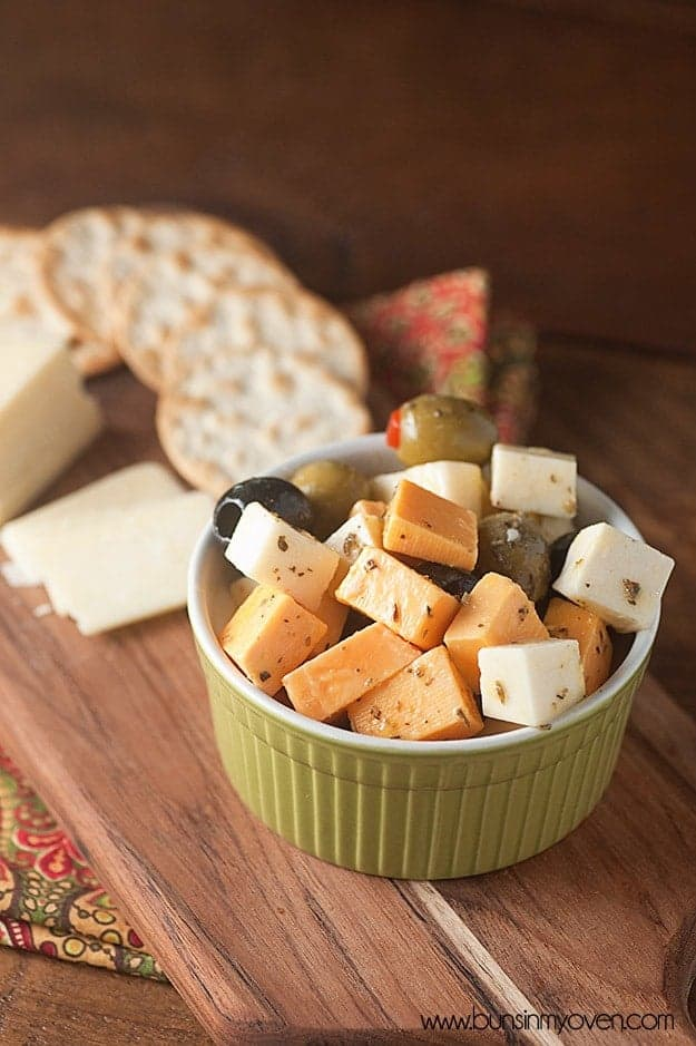 A cup of marinated cheeses and olives on a wooden cutting board