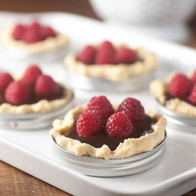Several raspberry tarts in mason jar lids on a white baking sheet.