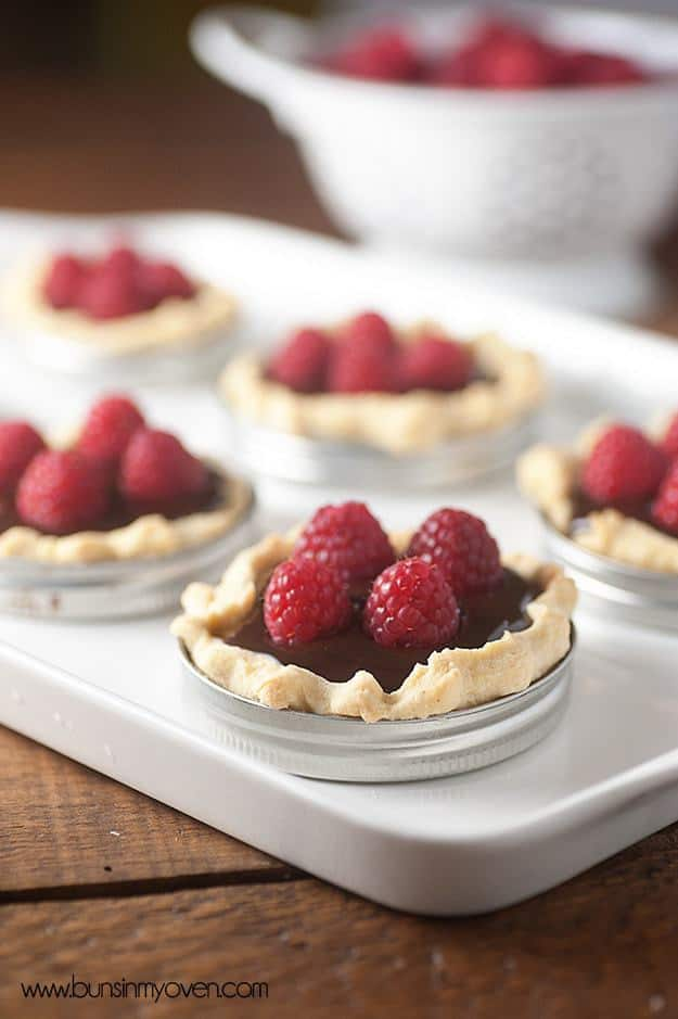 Mini chocolate tarts baked in a mason jar lid and topped with fresh berries!