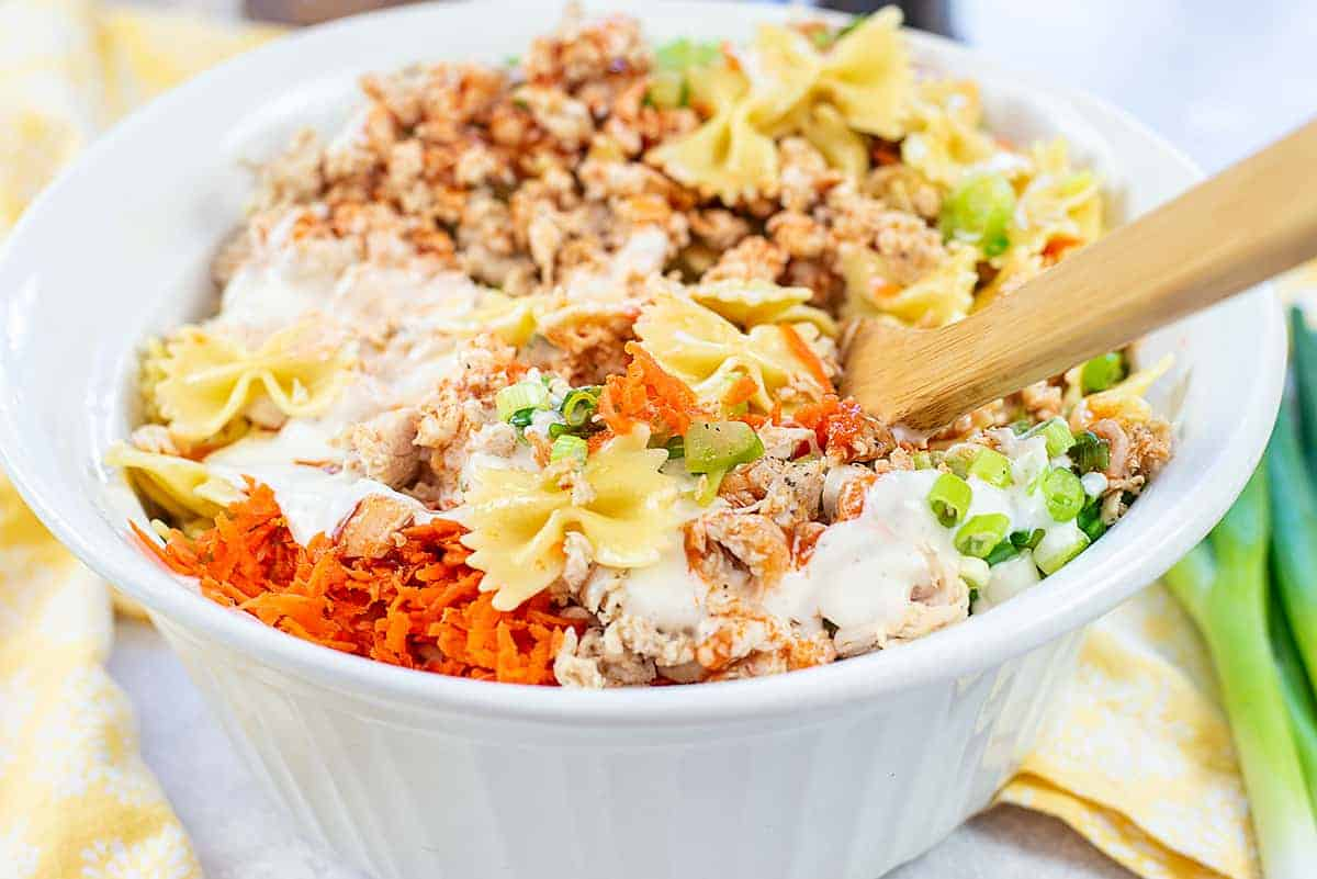ingredients for pasta salad in white mixing bowl.