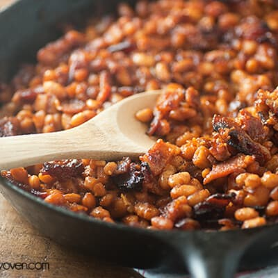 Baked beans being scooped out of a cast-iron skillet.