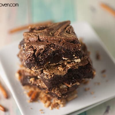 Three square peanut butter brownies on a square plate.