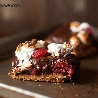 A close up of a raspberry smores bar on a thin baking sheet.