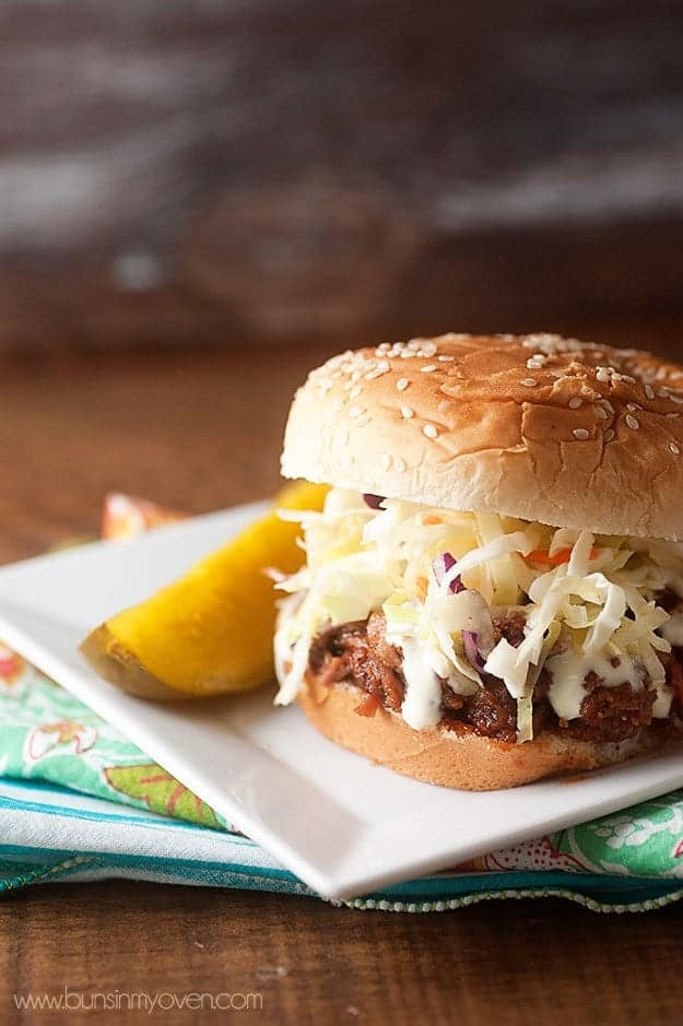 Pulled pork sandwiches topped with marinated slaw and white barbecue sauce! #slowcooker #crockpot #recipe #southernstyle