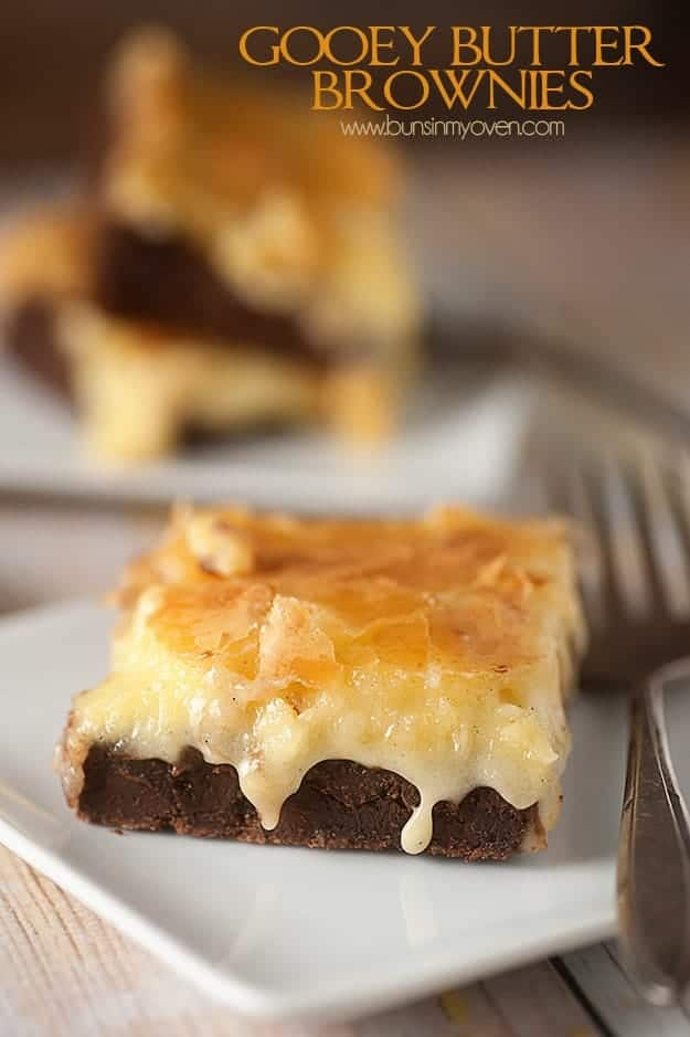 A close up of a gooey butter brownie on a whtie plate with a fork.