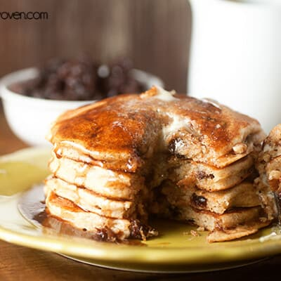 A bite has been cut out of a stack of raisin pancakes on a plate.