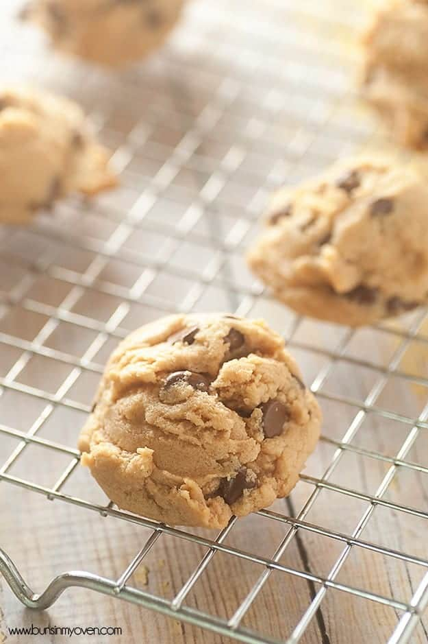 A close up of chocolate chip cookies resting on a wire cooling rack.